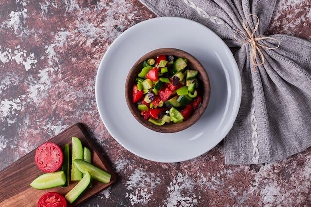 Salade De Légumes Dans Une Tasse En Bois Dans Une Assiette Blanche. Photo gratuit