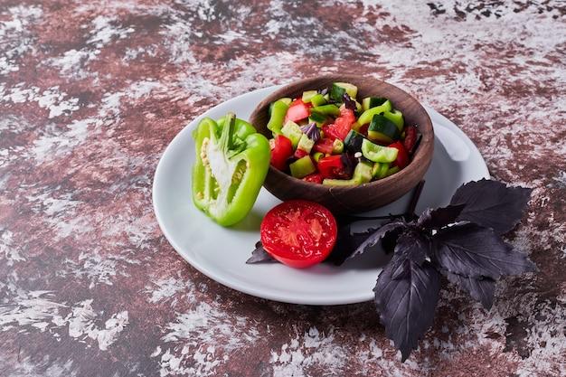 Salade De Légumes Dans Une Tasse En Bois Sur Le Marbre Au Milieu, Vue D'angle. Photo gratuit