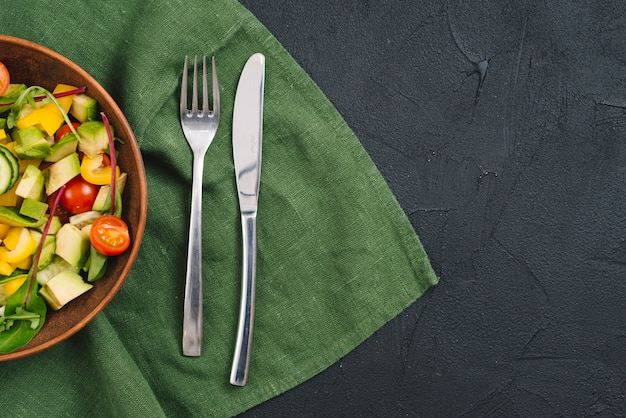 Salade de légumes sains avec une fourchette et couteau à beurre sur la nappe sur fond de béton noir Photo gratuit