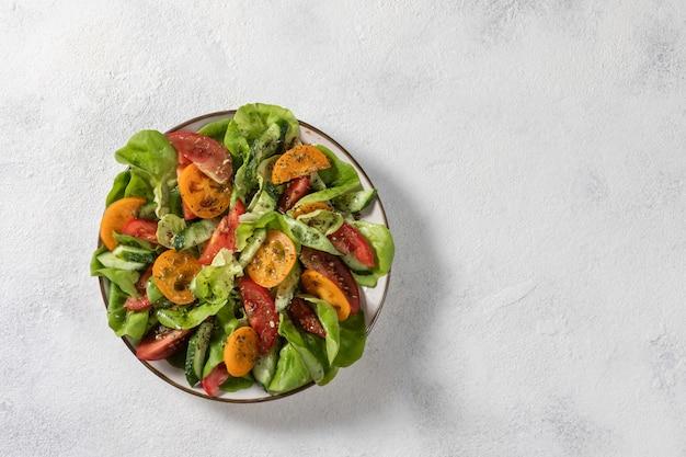 Salade de légumes sains de légumes frais de tomates, concombres, oignons, épinards, laitue sur une assiette. menu de régime. vue d'en-haut. Photo Premium