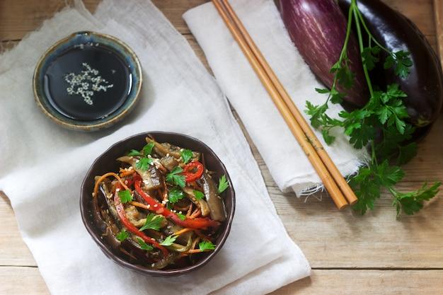 Salade de légumes de style oriental aux aubergines, sauce soja et baguettes sur une table en bois. style rustique. Photo Premium