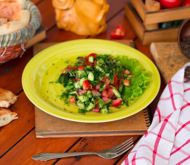 Salade de légumes verts, choban salati dans la plaque verte. Photo gratuit