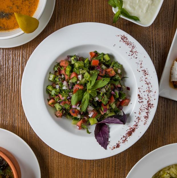 Salade de légumes verts vue de dessus avec les cubes à l'intérieur de la plaque blanche. Photo gratuit