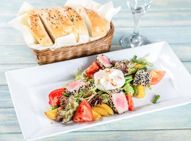 Salade niçoise au thon grillé et oeuf poché sur une table en bois Photo Premium