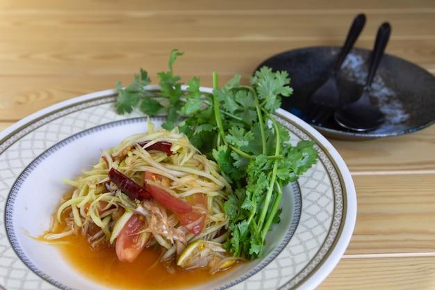 Salade De Papaye Et De Coriandre Dans Un Plat Prêt à Manger Sur La Table, La Nourriture Populaire Asiatique. Photo Premium
