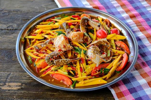 Salade de papaye à la mangue avec crabe bleu placé dans un plateau magnifiquement placé sur une table en bois de style thaï Photo Premium