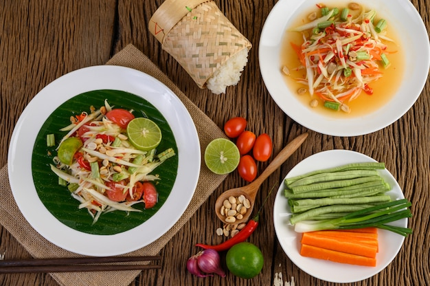 Salade De Papaye (som Tum Thai) Sur Une Plaque Blanche Sur Une Table En Bois. Photo gratuit