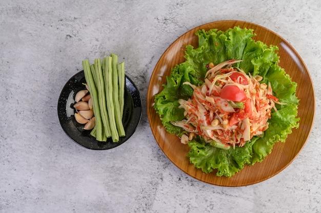 Salade De Papaye Thaï Dans Une Assiette Blanche Avec Des Haricots Verts, De L'ail Et Du Chou Blanc Photo gratuit