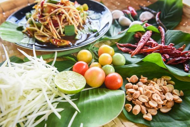Salade de papaye verte, cuisine thaïlandaise épicée aux herbes et épices, ingrédients avec cacahuètes tomates chili Photo Premium