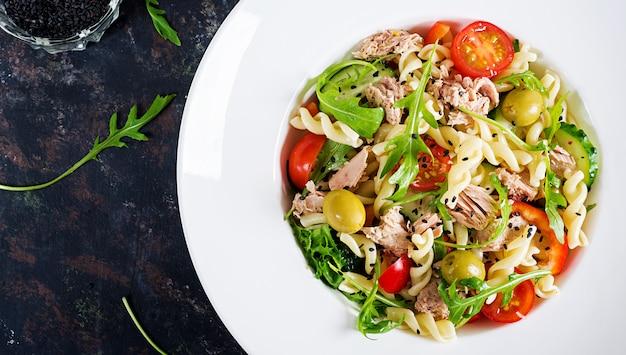 Salade de pâtes au thon, tomates, olives, concombre, poivron et roquette sur fond rustique Photo Premium