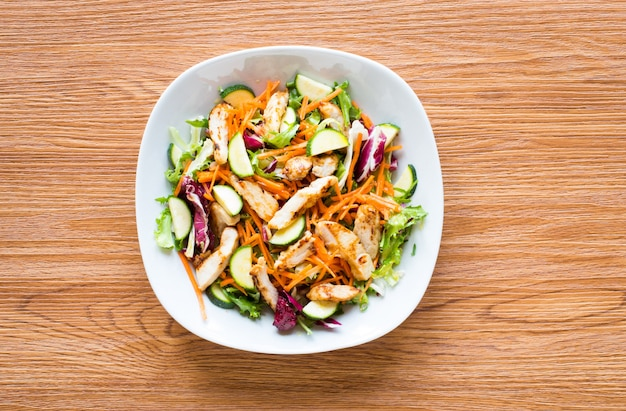 Salade de poitrine de poulet avec courgettes et tomates cerises, sur une table en bois Photo Premium