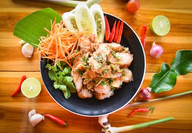 Salade de porc grillée cuisine thaïlandaise servie à table avec des ingrédients à base d'herbes et d'épices. Photo Premium