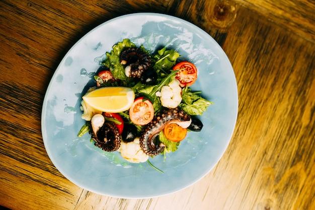 Salade avec poulpe et chou-fleur sur l'assiette. Photo Premium