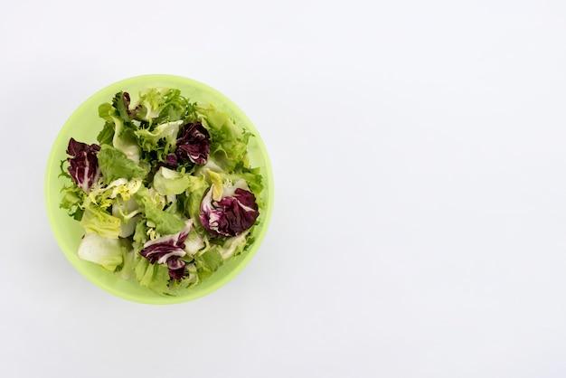 Salade saine dans un bol sur fond blanc Photo gratuit