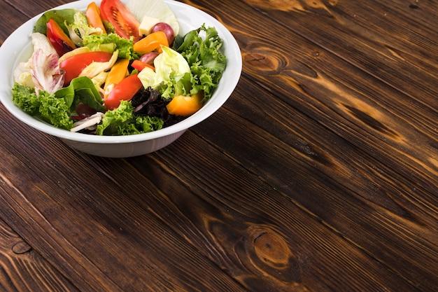 Salade saine sur fond en bois Photo gratuit