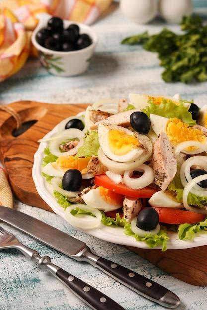 Salade saine de laitue biologique au poulet, tomates, œufs, olives noires et oignons blancs Photo Premium