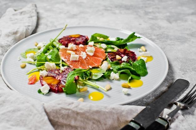 Salade saine avec de la roquette, du pamplemousse, des oranges rouges, des noix et du tofu. Photo Premium