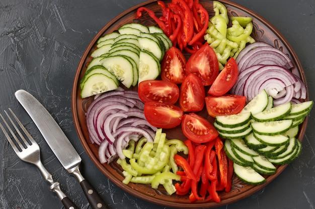 Salade saine de tomates, oignons rouges, poivrons et concombres sur assiette sur dark Photo Premium