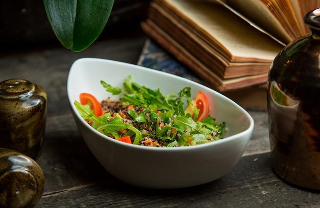 Salade de saison avec des feuilles de roka et des tranches de tomate Photo gratuit