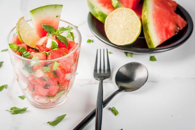 Salade De Salsa De Légumes Au Melon D'eau, Tomates, Oignons, Légumes Verts, Citron Vert En Verre Portionné Photo Premium