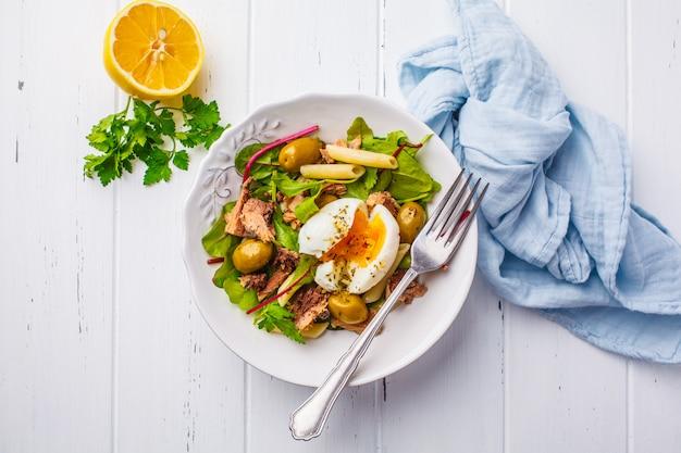 Salade de thon avec pâtes, olives et œuf poché dans une assiette blanche sur du bois blanc Photo Premium