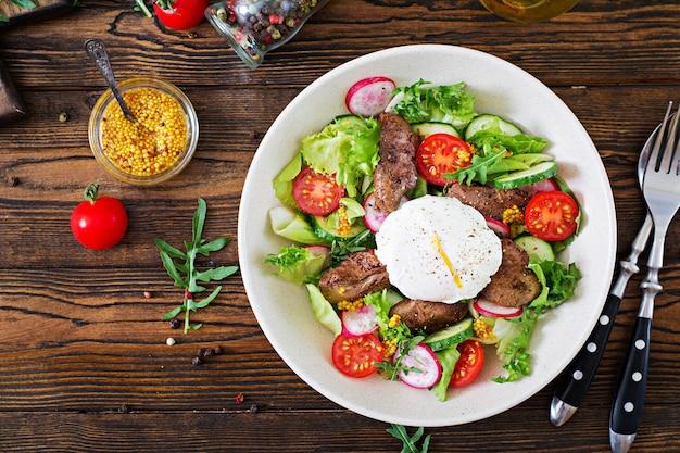 Salade tiède de foie de poulet, radis, concombre, tomate et œuf poché. la nourriture saine. haut Photo Premium