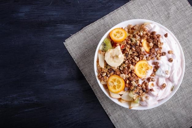 Salade végétarienne de bananes, pommes, poires, kumquats, kiwi au granola et yaourt sur bois noir Photo Premium