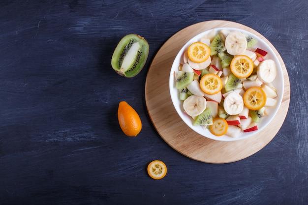 Salade végétarienne de bananes, pommes, poires, kumquats et kiwis sur fond noir en bois. Photo Premium