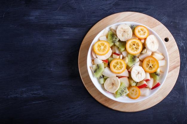 Salade végétarienne de bananes, pommes, poires, kumquats et kiwis sur une table en bois noire. Photo Premium