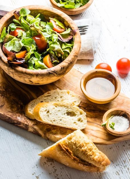 Salade végétarienne avec laitue et tomates dans un bol en bois d'olivier Photo Premium
