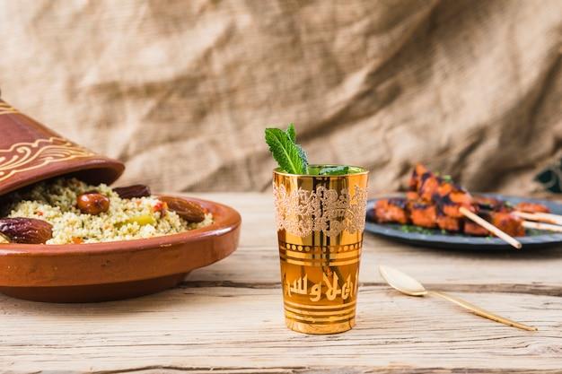 Salade de viande grillée et de quinoa aux prunes séchées près de la tasse sur la table Photo gratuit