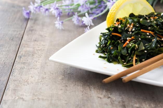 Salade De Wakame Avec Carotte, Graines De Sésame Et Jus De Citron Sur L'espace De Copie De Table En Bois Photo Premium