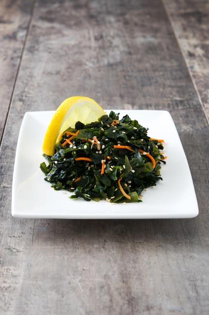 Salade De Wakame Avec Carotte, Graines De Sésame Et Jus De Citron En Plaque Sur Table En Bois Photo Premium