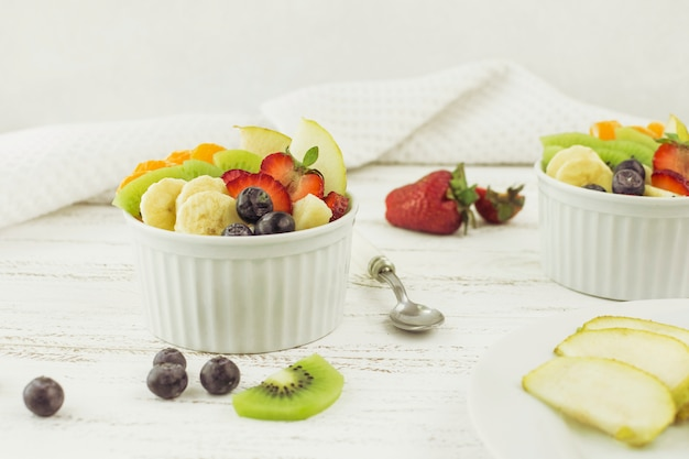 Salades de fruits savoureuses entourées de fruits Photo gratuit