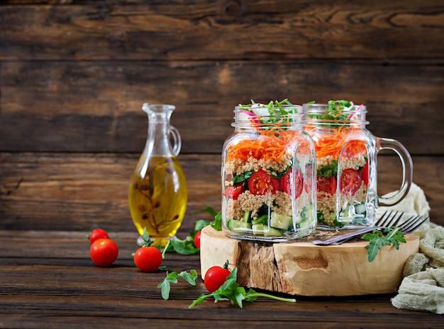 Salades de quinoa, roquette, radis, tomates et concombre dans des bocaux en verre sur dos en bois Photo Premium