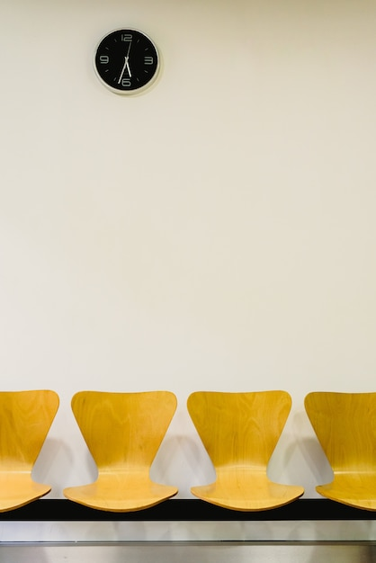 Salle d'attente avec des chaises en bois vides et horloge murale, concept en attente. Photo Premium