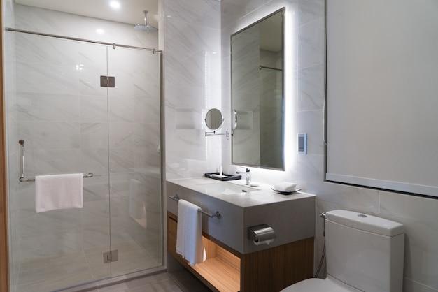 Salle de bain contemporaine éclairée avec des serviettes propres accrochées aux poignées Photo Premium