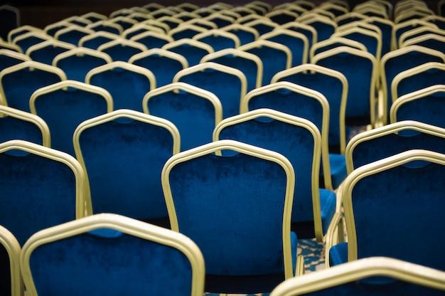 Salle De Cinéma Vide. Un Grand Nombre De Chaises En Velours Bleu Dans Une Rangée. Photo Premium