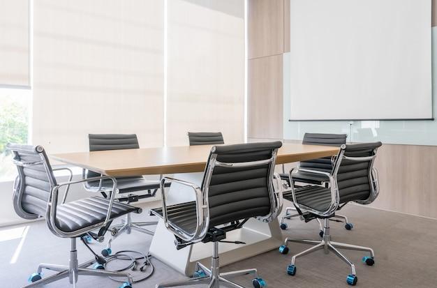 Salle de réunion moderne avec écran de projection et table de conférence Photo Premium