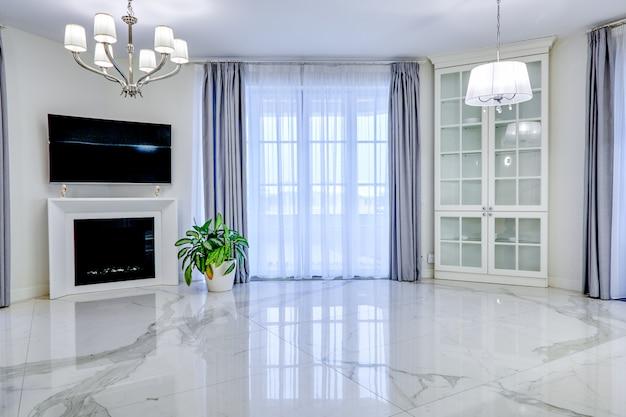 Salle de séjour intérieure minimaliste dans les tons clairs avec sol en marbre, grandes fenêtres et cheminée sous la télévision Photo Premium