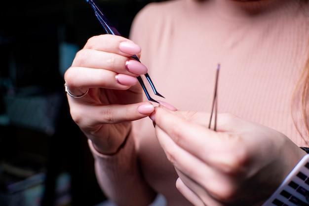 Salon de beauté, procédure d'extension de cils se bouchent. belle femme aux cheveux longs Photo Premium