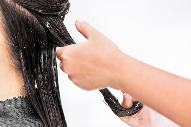 Salon de coiffure appliquant un traitement capillaire. appliquer une couleur crème sur les cheveux. Photo Premium