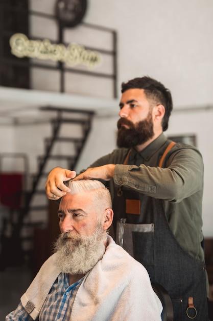 Salon de coiffure corrigeant sa coiffure en client Photo gratuit