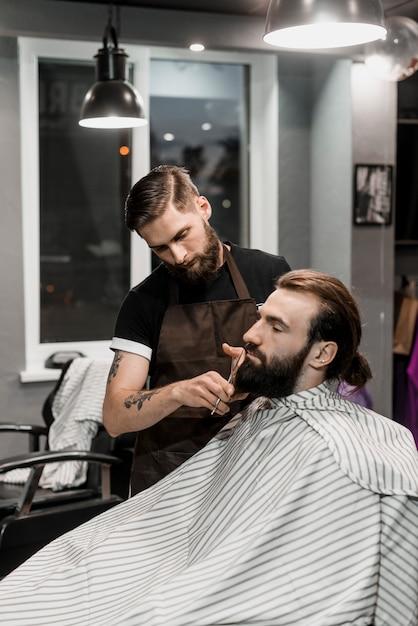 Salon de coiffure coupe la barbe du client dans le salon de coiffure Photo gratuit