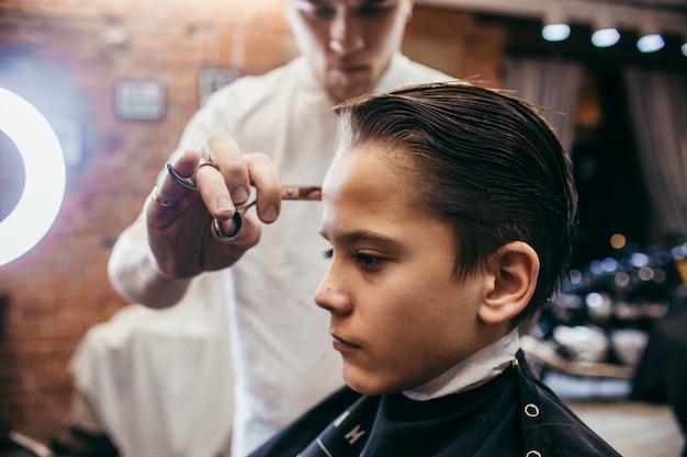 Salon De Coiffure Coupe De Cheveux Adolescent Dans Le Salon De Coiffure Photo Premium