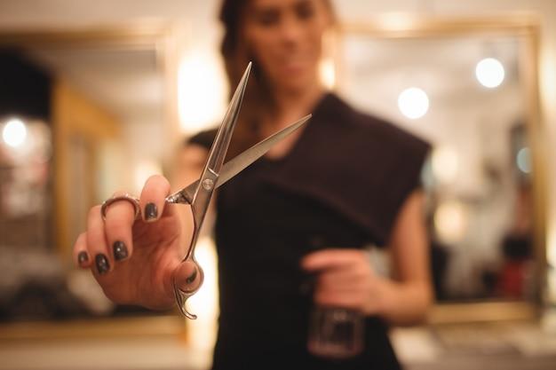 Salon de coiffure femme tenant des ciseaux Photo gratuit