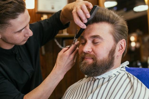 Salon De Coiffure Un Homme Avec Une Barbe Coupe Coiffeur Beaux Cheveux Et Soins Salon De Coiffure Pour Hommes Photo Premium
