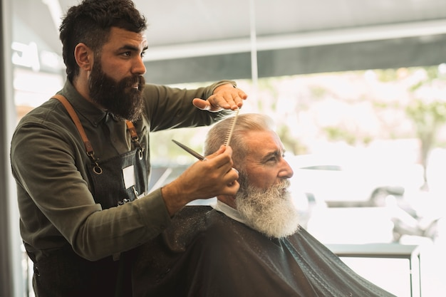Salon de coiffure pour hommes peignant les cheveux d'un client âgé dans le salon de coiffure Photo gratuit