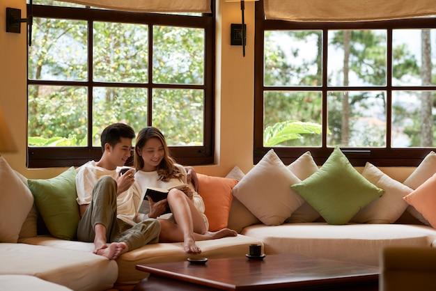 Salon avec fenêtres panoramiques et couple romantique assis sur un grand canapé, lisant un livre ensemble Photo gratuit