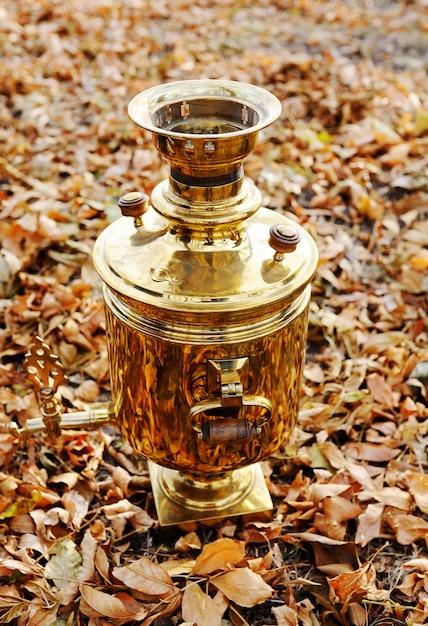 Samovar doré sur fond de feuilles d'automne Photo Premium